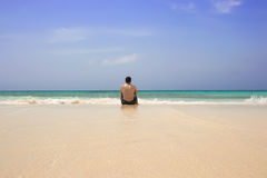 Man sitting lonely on beach Royalty Free Stock Images