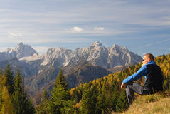 Man sitting and looking at mountains Stock Images