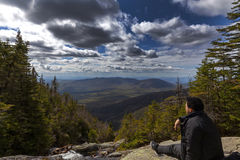 Man sitting and looking out from elevation on Mount Washinton vi. A Ammonoosuc ravine trail in Coors County,  New Hampshire Royalty Free Stock Photo