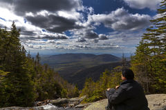 Man sitting and looking out from elevation on Mount Washinton vi. A Ammonoosuc ravine trail in Coors County,  New Hampshire Royalty Free Stock Photography