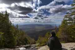 Man sitting and looking out from elevation on Mount Washinton vi. A Ammonoosuc ravine trail in Coors County,  New Hampshire Royalty Free Stock Images