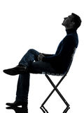 Man sitting looking up  silhouette full length Stock Photo