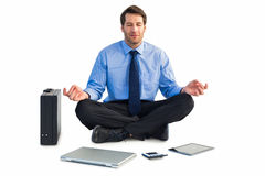 Man sitting in lotus pose with laptop, tablet and suitcase Royalty Free Stock Images