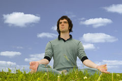 Man sitting in the lotus posture. On the grass Royalty Free Stock Images