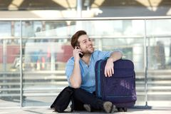 Man sitting with luggage and talking on mobile phone. Portrait of a smiling man sitting with luggage and talking on mobile phone at airport Stock Photos