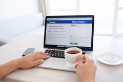 man sitting at the MacBook retina with site Facebook on the screen and drinking tea stock photos