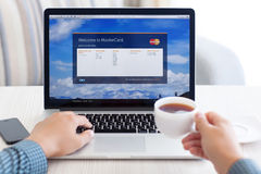 Man sitting at the MacBook retina with site MasterCard on the sc Stock Photos