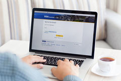 Man sitting at the MacBook retina with site Visa on the screen Stock Photos