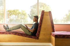 Man Sitting on Maroon and Brown Fabric Padded Sofa Using Laptop Beside Glass Window royalty free stock photography