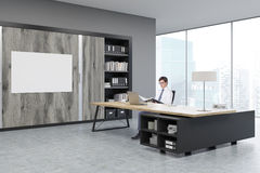 Man sitting at a massive CEO table. Man sitting in a CEO office at a massive wooden table. There are wooden doors and a horizontal poster on the wall. 3d Royalty Free Stock Photos