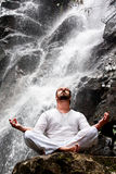 Man sitting in meditation yoga on rock at waterfall in tropical Stock Image