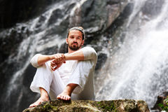 Man sitting in meditation yoga on rock at waterfall in tropical. Rainforest royalty free stock photos