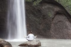 Man sitting in meditation yoga on rock at waterfall Tibumana. Man sitting in meditation yoga on rock at waterfall in tropical. Tibumana Waterfall royalty free stock images