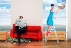 Man sitting on a  money pile while woman is doing chores Stock Image