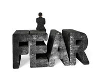 Man sitting on mottled 3D fear concrete word Stock Photo