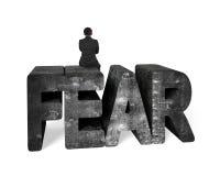 Man sitting on mottled 3D fear concrete word Stock Photo