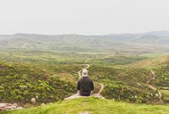 Man Sitting on Mountain Facing Forest Field stock image