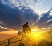 Man sitting on a mountain top Royalty Free Stock Images