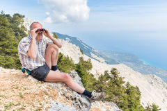 Man sitting in mountains looking through binoculars Royalty Free Stock Image