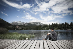 Man sitting near alpine mountain lake. Man sitting on the bank of alpine mountain lake Royalty Free Stock Photography