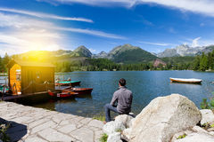 Man sitting near alpine mountain lake. At sunny day Stock Photo