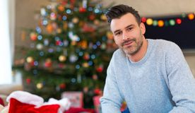 Man sitting near a Christmas tree. At home Stock Images