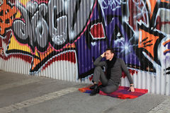 Man sitting near graffiti wall Royalty Free Stock Images