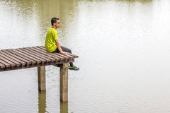 Man sitting near lake stock photo