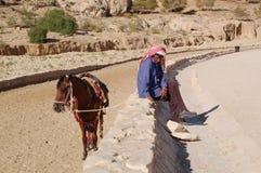 Man sitting near a mule Stock Photos