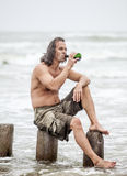 Man sitting near the sea and drinking alcohol Royalty Free Stock Photos