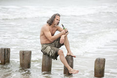 Man sitting near the sea and drinking alcohol Royalty Free Stock Images