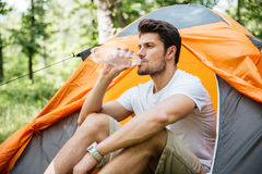 Man sitting near touristic tent and drinking water in forest Stock Image