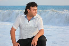 Man is sitting near water on sea coast. Royalty Free Stock Photos