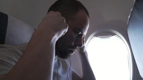 Man sitting near the window of flying airplane and listening to music on headphones with your smartphone. stock footage stock footage