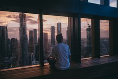 Man sitting near a window at the top of a tall building with the view of urban city tall buildings royalty free stock photo