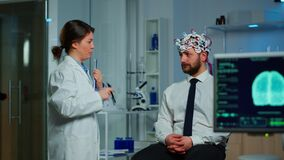 Man sitting on neurological chair with brainwave scanning headset