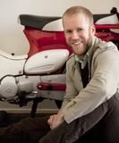 Man is sitting next red and white scooter. Stock Photo