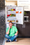 The man sitting next to open refrigerator Stock Photography