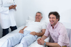 Man sitting next to patient smiling. In hospital Royalty Free Stock Images