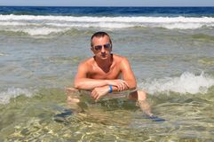 Man sitting in the ocean stock photography