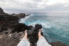 Man sitting on ocean cliff edge wearing flip flops and shorts. stock image