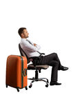 Man sitting on office chair with suitcase Stock Photography