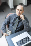 Man sitting at office desk. Businessman with laptop computer sitting at office workstation stock images