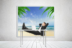 Man sitting in the office and dreaming about holidays on a beach Royalty Free Stock Image