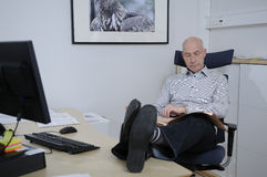 Man sitting in office and reading the newspaper. A bald man sitting at the office Royalty Free Stock Images