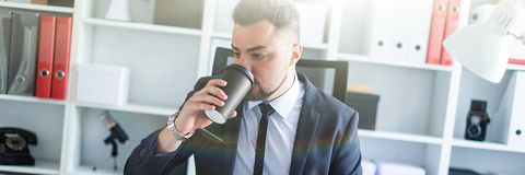 A man is sitting in the office at the table and drinking coffee from a glass. A bearded man with a business suit is working in a bright office. photo with depth stock photo
