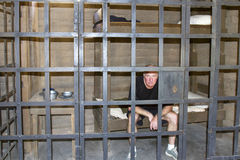 Man Sitting in Old Time jail. Man sitting on a cot in prison cell in old west jail stock photos