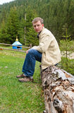 Man sitting on an old tree trunk Stock Image