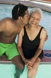 Man Sitting On Edge Of Swimming Pool Kissing Mother On Cheek Elevated View. Royalty Free Stock Photography