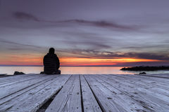 Free Man Sitting On The Pier And Watching The Sunset Royalty Free Stock Photography - 70257807